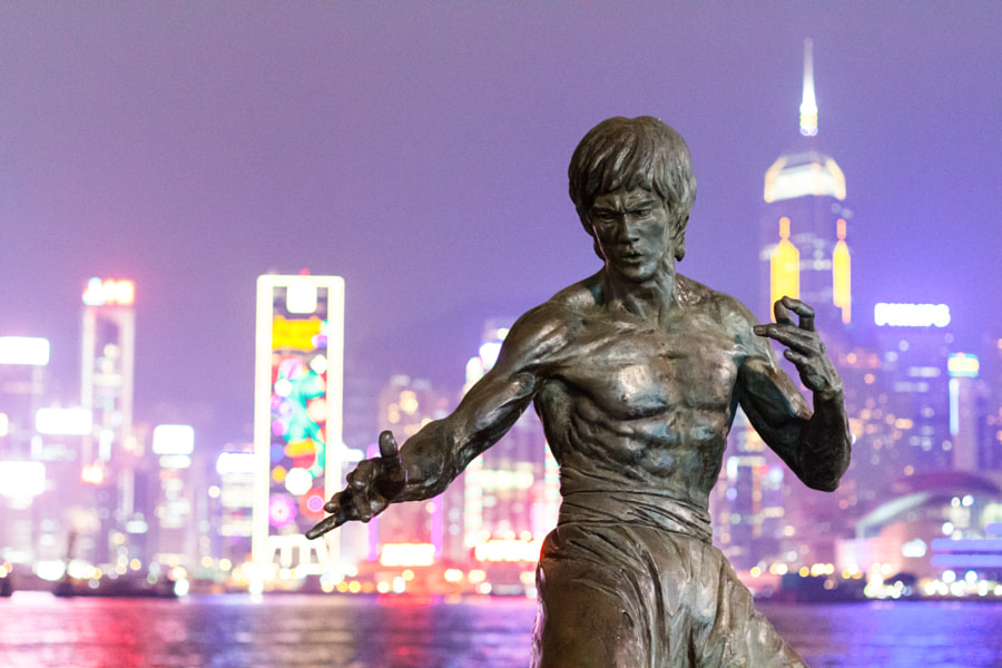Bruce Lee statue in Avenue of Stars with Hong-Kong skyline in the background by night.