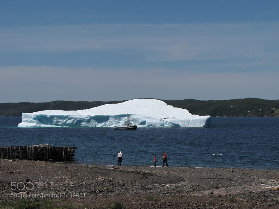 """This """"small"""" iceberg off Britannia dwarfs the boat in front of it and the people on the beach."""