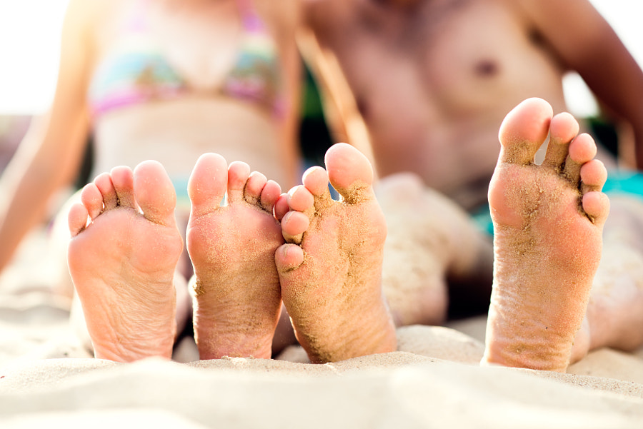 Feet of unrecognizable couple sitting on the sandy beach by Jozef Polc on 500px.com