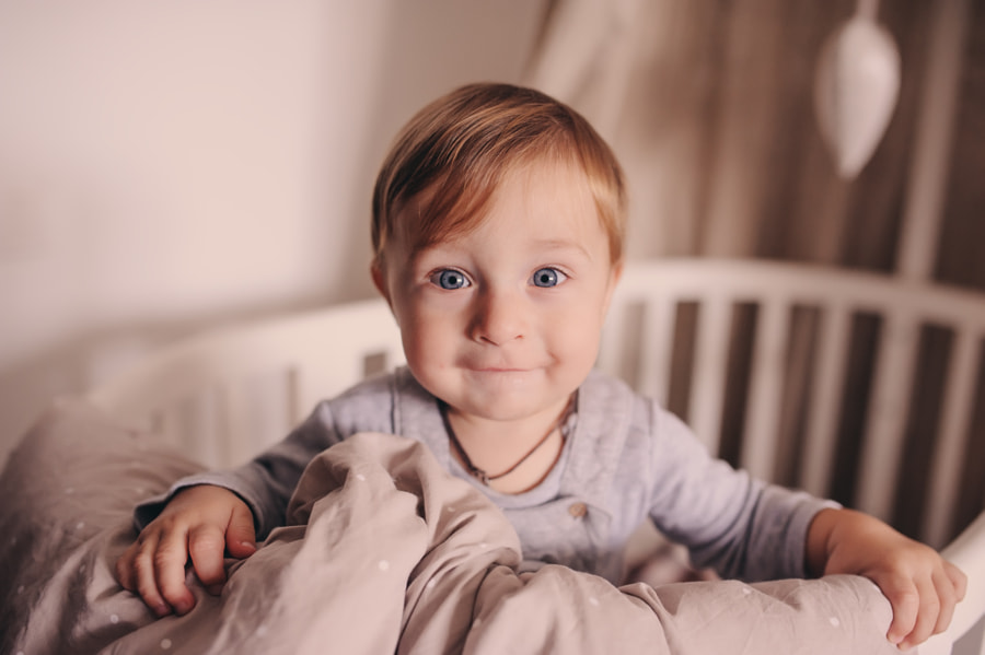 cute happy baby boy awake in his bed in the morning and playing. Candid capture in real life... by Мария Евсеева on 500px.com