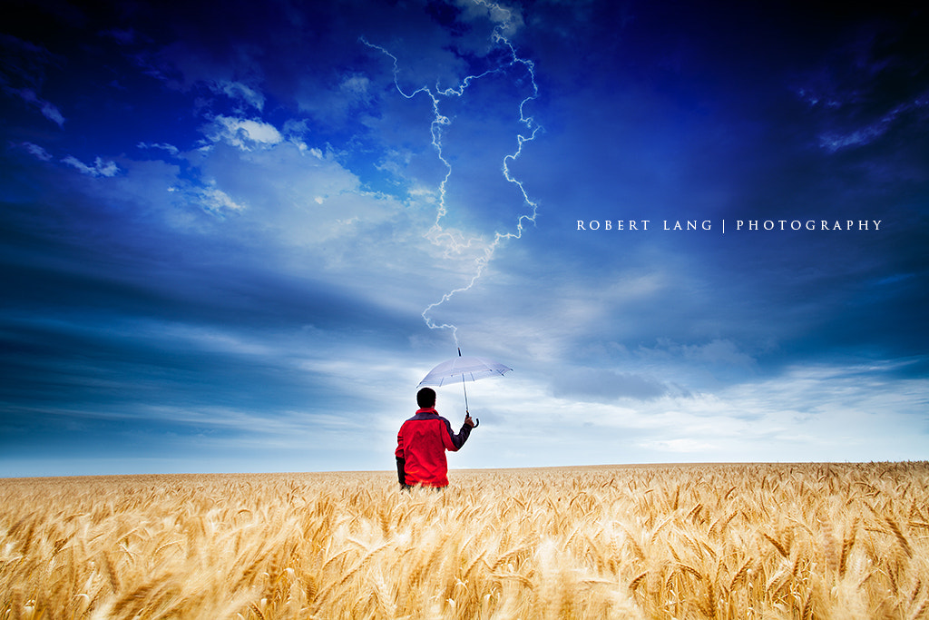 Photograph Lightning striking man standing in wheat field holding an umbrella  by Robert Lang on 500px
