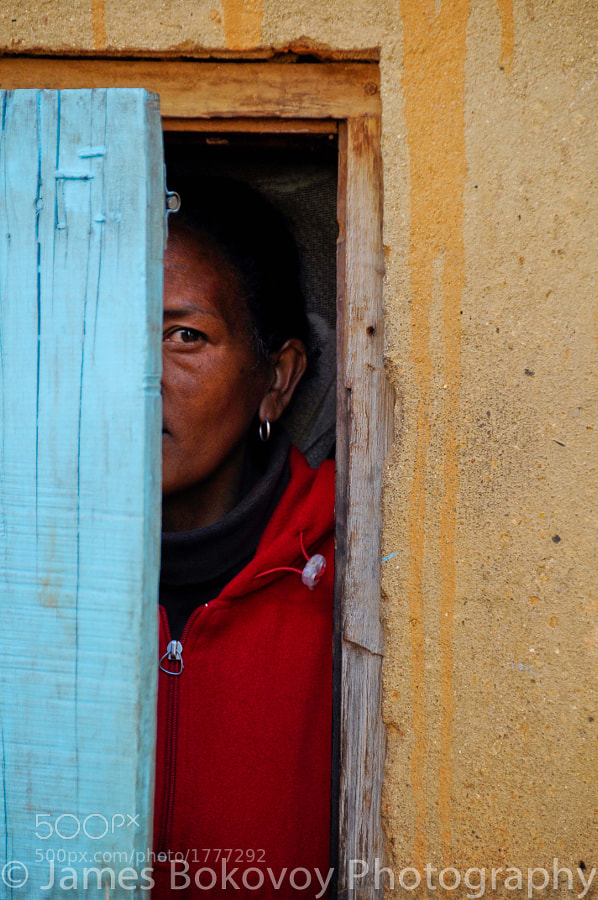 A shy Malagasy woman watches people walk by her home from behind a colorful blue door in Antananarivo, Madagascar.