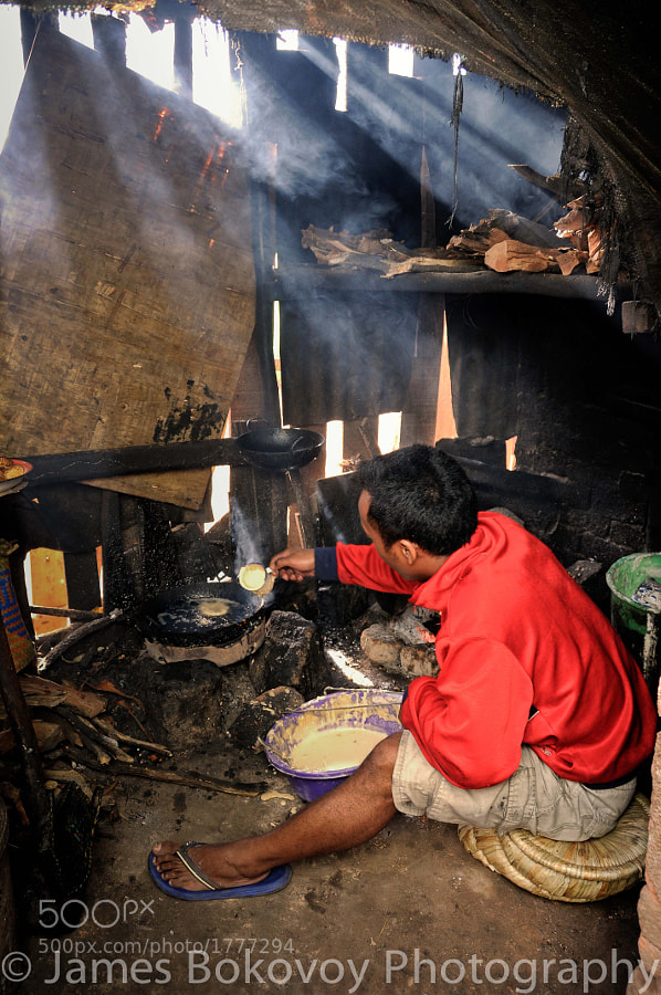 A young Malagasy man fixes food to sell in his families shop in Antananarivo, Madagascar.