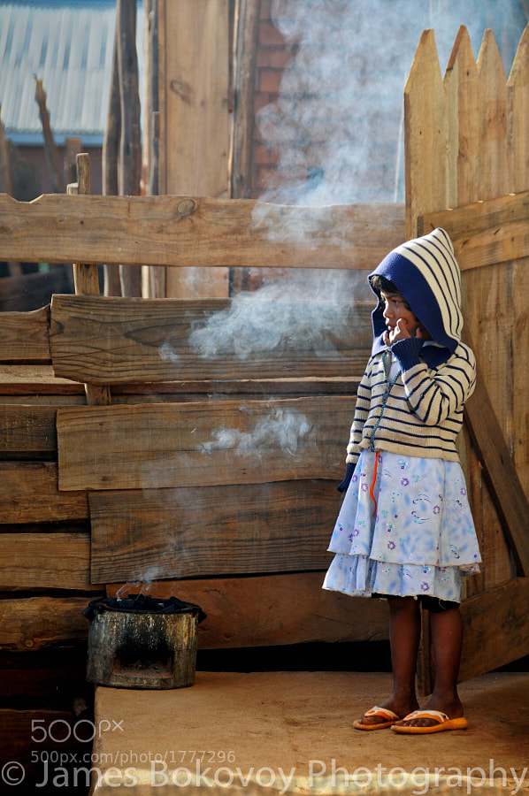 A young Malagasy girl stands by a small charcoal pot as she waits for breakfast in Antananarivo, Madagascar.