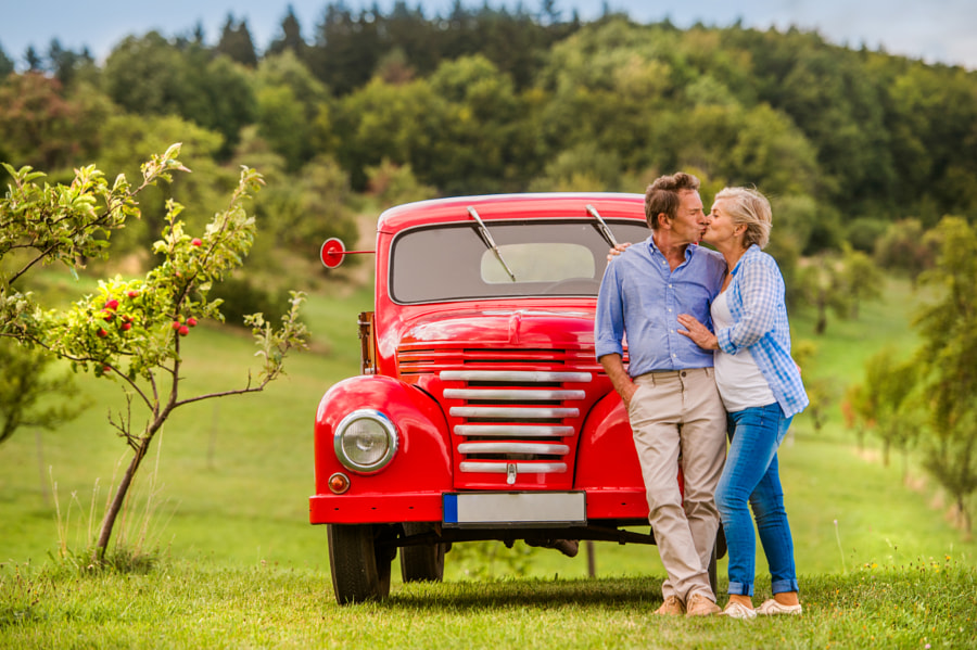 Senior couple hugging and kissing, vintage car, sunny nature by Jozef Polc on 500px.com