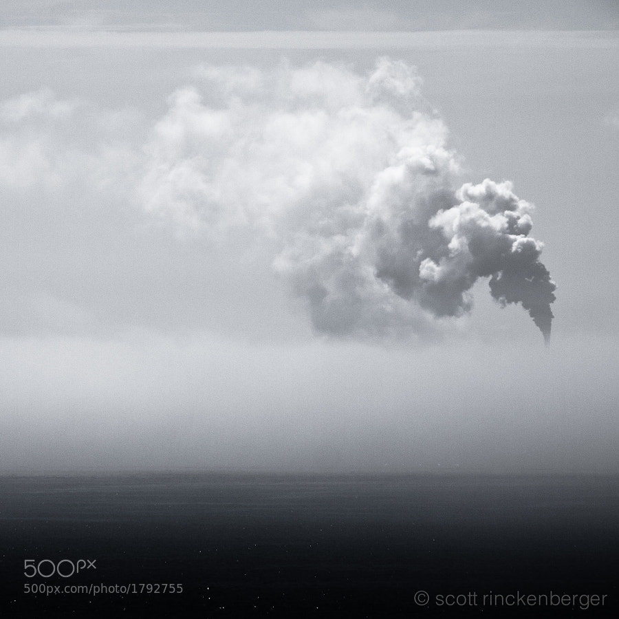 The fog in this image has enveloped a large oil refinery, leaving the giant plume of steam from the smoke stacks as the only evidence of it's presence.