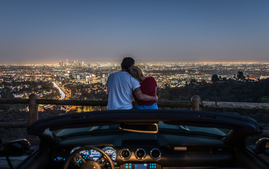 Couple enjoying skyline view from their car by Cristian Negroni on 500px.com