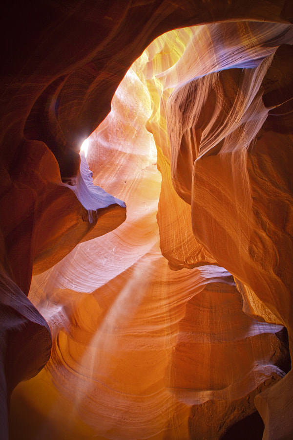 A shaft of diffused light illuminates an opening in a slot canyon in Arizona.