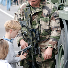 A young boy learns about weapons at a French armed forces exhibition as his sister looks on.
