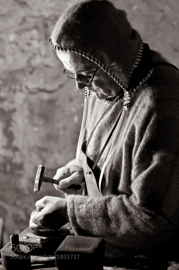 Leather worker in medieval outfit in his workshop