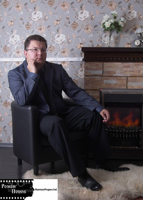 Photograph The businessman sits near a fireplace. by Roman Popov on 500px