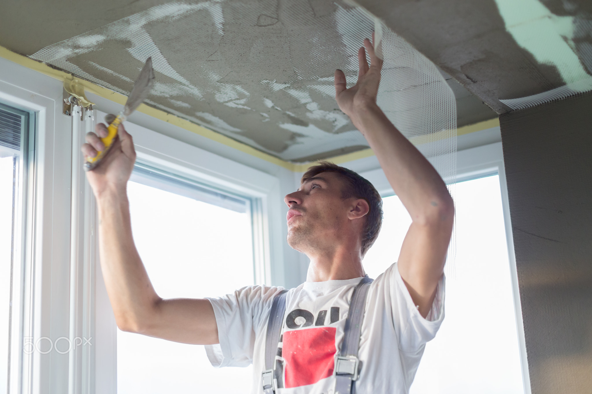 Plasterer renovating indoor walls and ceilings. Finishing works.