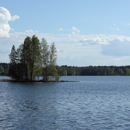 Small island in blue lake in summer