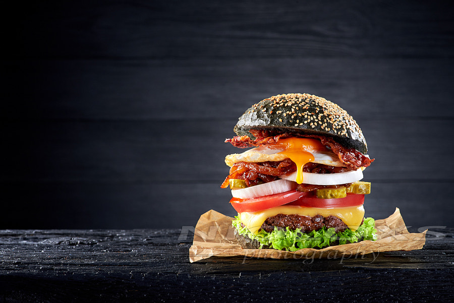 Black burger with egg and bacon on the wooden table by Kamil Zab?ocki on 500px.com