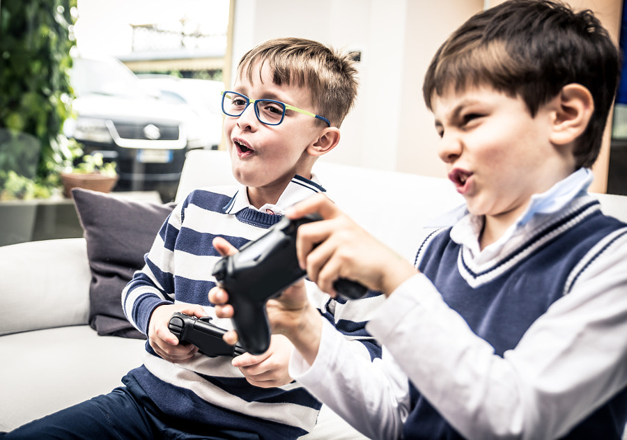 Happy children playing videogames in the living room by Cristian Negroni on 500px.com