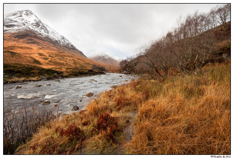 The river Etive entering the Glen Etive. Morning light on the snow caped mountains.