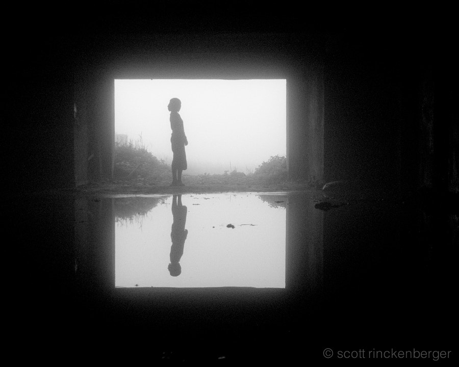 A reflected silhouette in a the flooded basement of an abandoned hotel in Cambodia.