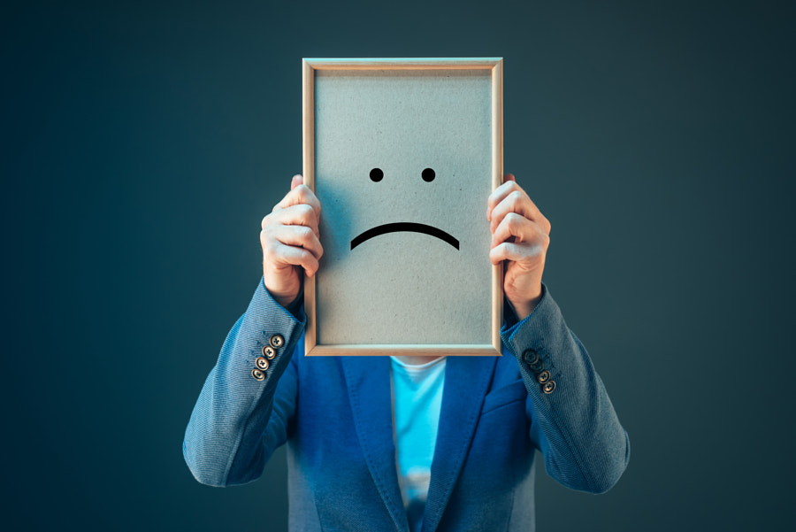 Businesswoman is pessimistic, holding smiley emoticon over face by Igor Stevanovic on 500px.com