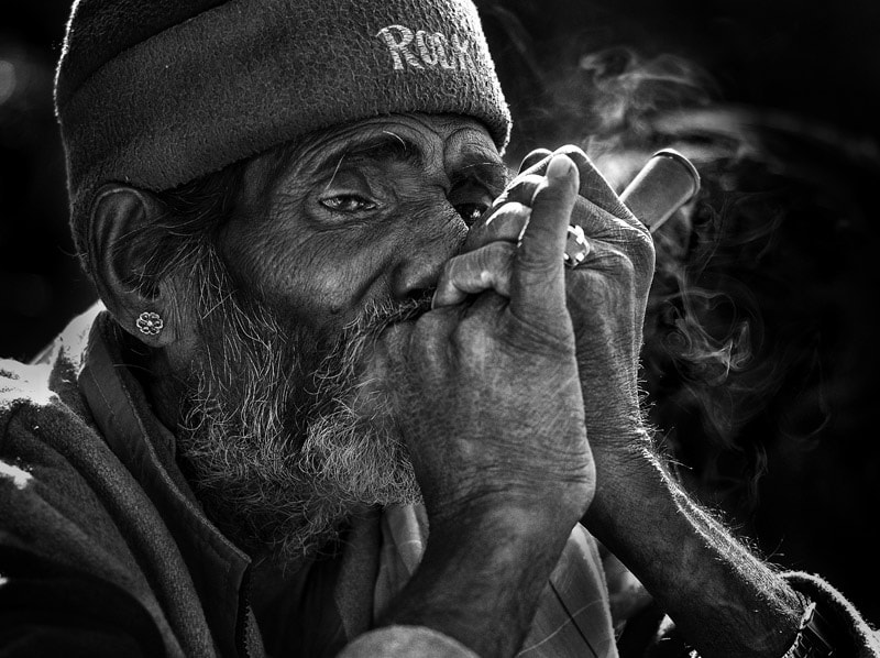 an indian man smoking chillum in Pushkar, India