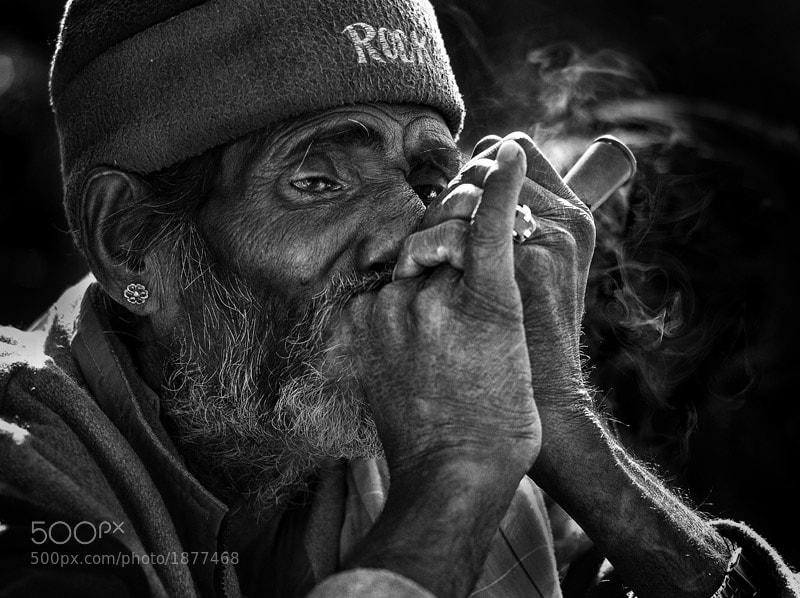 an indian man smoking chillum in Pushkar, India