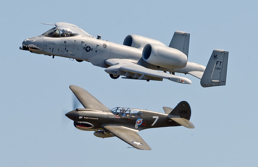 The original plane flown by the Flying Tigers, the P-40 Warhawk flys along side the current plan flown by the Flying Tigers, the A-10 Thunderbolt II (aka Warthog)