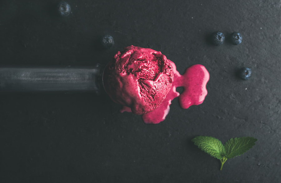 Melting scoop of blueberry ice-cream over black slate stone background by Anna Ivanova on 500px.com
