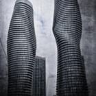 """The Absolute Condos is a five-tower glass, concrete and steel development near Mississauga's town center. With its twisting rhythms resembling the human body, the first Absolute Tower has been nicknamed Marilyn Monroe by the locals. The entire 56-story building rotates by different degrees at different level, which corresponds with sceneries at different height. Unlike the South tower, which gets thinner in the middle as it rises, Absolute North instead gets larger in the middle, which has resulted in some members of the public calling them the """"condo couple"""" with the South Tower being the sexy female and the North Tower the more robust man."""