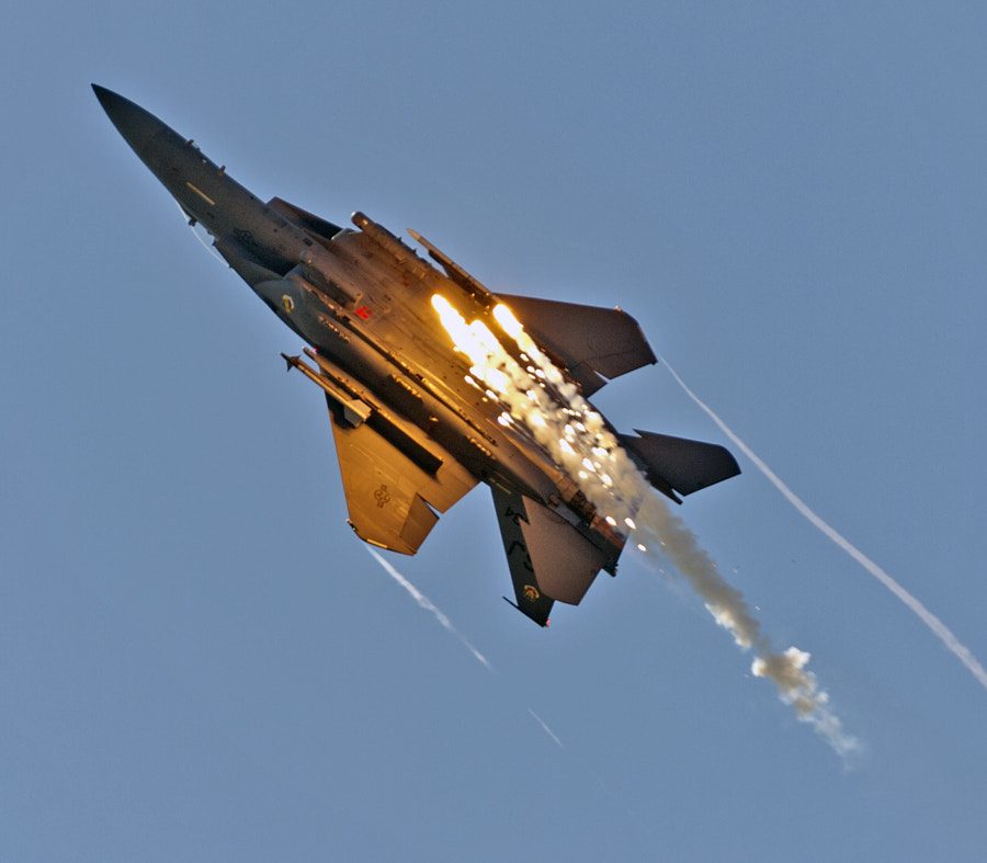 An F-15E releases flares as it rolls over.