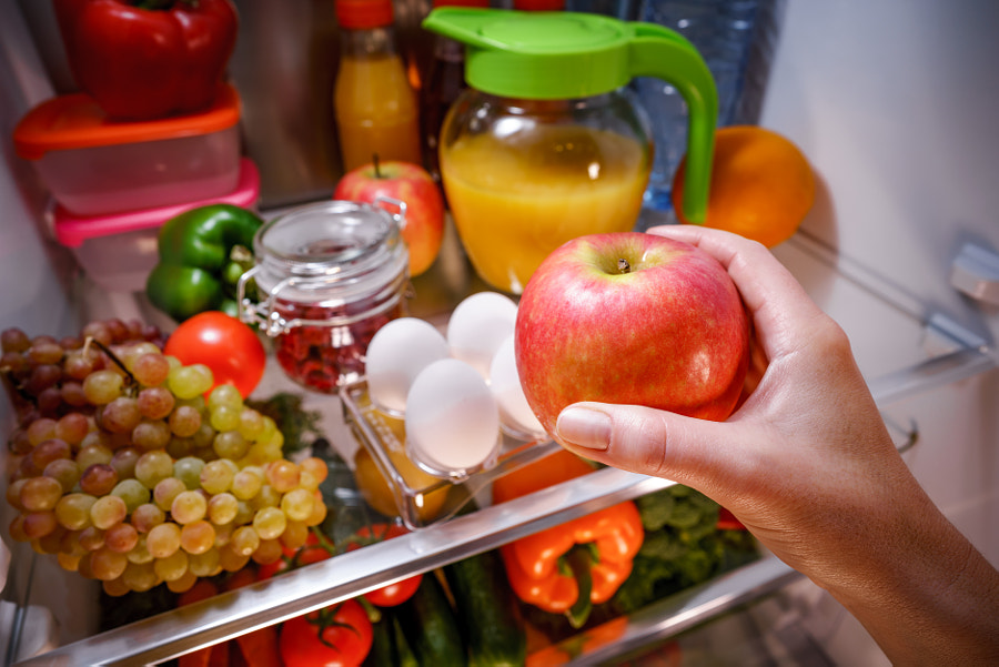 Woman takes the apple from the open refrigerator. by Andrey Armyagov on 500px.com