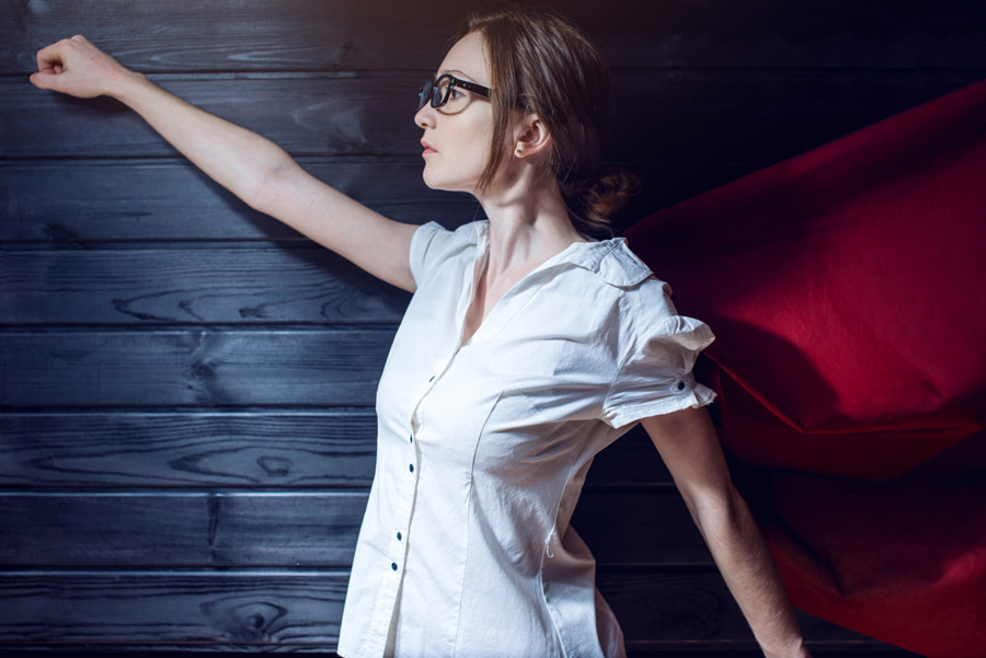 Superwoman office worker standing in a suit and red cloak by Artem Oleshko on 500px.com