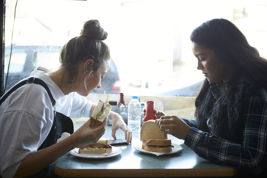 Two Female Students Eating Meal In Café by Guerilla Images on 500px.com