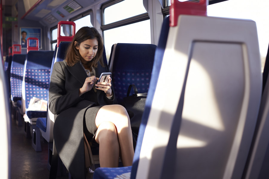 Businesswoman Reading Text Message On Train During Commute by Guerilla Images on 500px.com