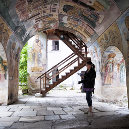 Tourist under polychrome arches of a monastery