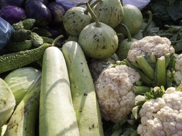 Varied raw vegetables being displayed on an open cart for sale