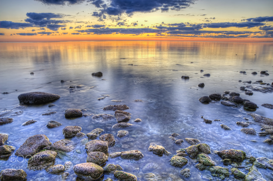 The sun is just about to peak over the horizon.  You can purchase this photo here:  http://fineartamerica.com/featured/sunrise-over-the-rocks-scott-norris.html.