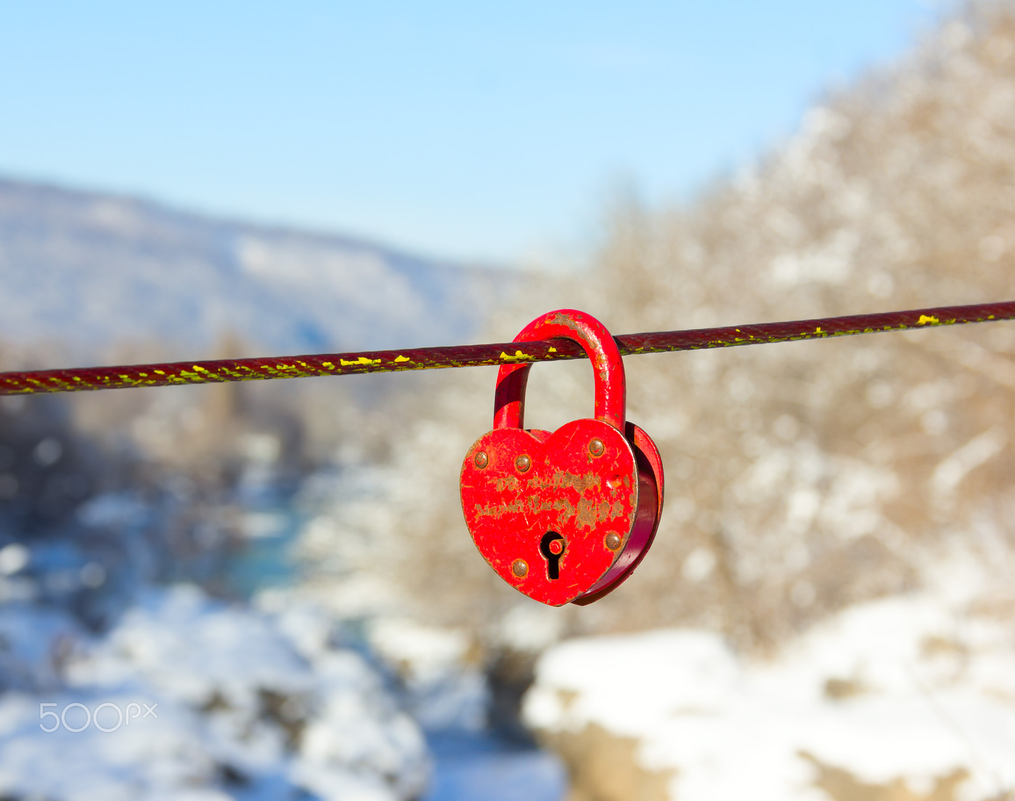 old closed red padlock in heart shape on a background of a winter mountain landscape close up