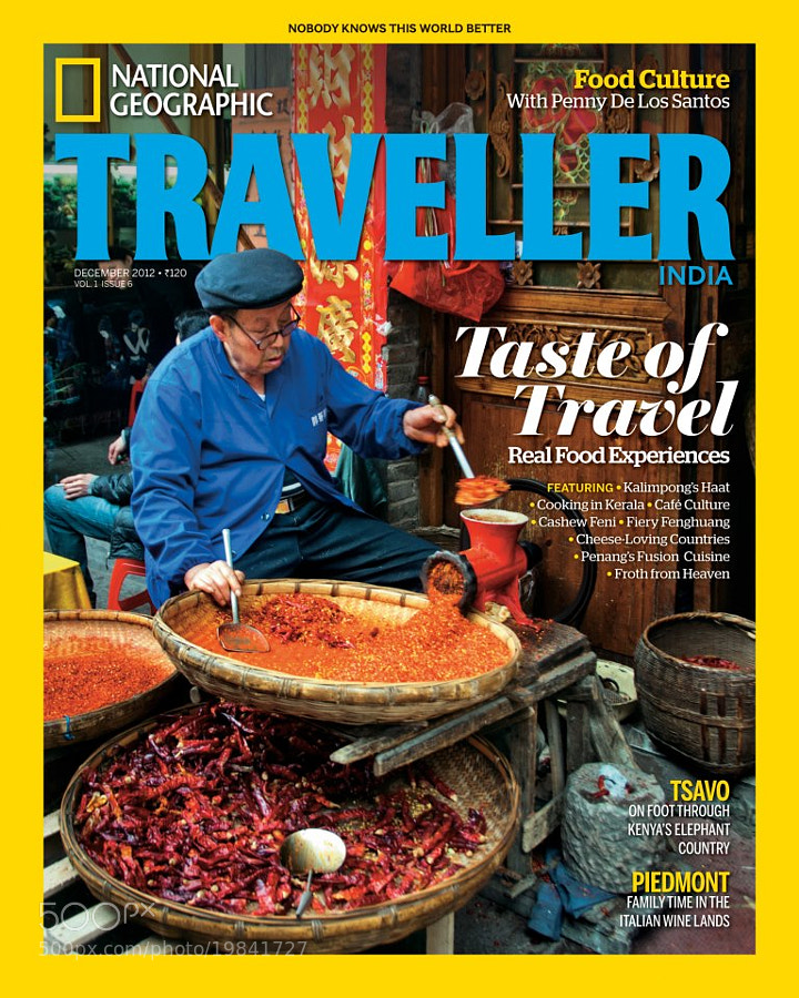 """On The Cover:<br/>This photograph was taken at the food market in Fenghuang, China. intrigued by this old man meticulously grinding chillies, outside his spice store, Vladimr Popov, the photographer, called him the """"spicy Food Guru""""."""