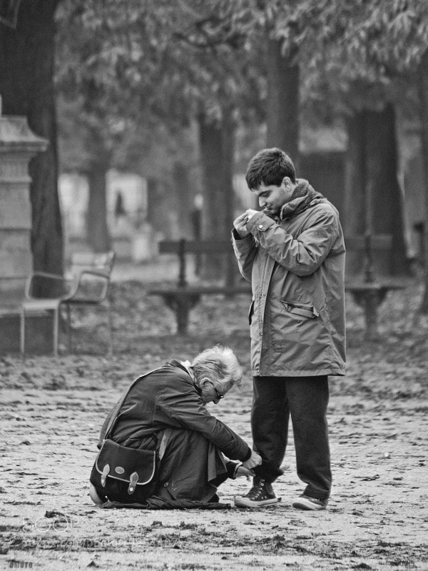 A mother is lacing her son's shoes at the Luxembourg's park.