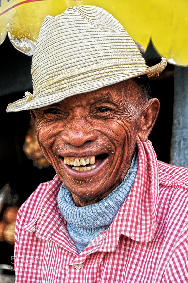 A friendly Malagasy man shares a smile with a stranger. As I returned the gesture we are no longer stingers, but friends.