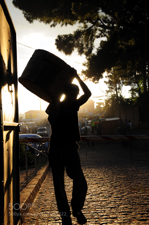 A worker in Antananarivo, Madagascar carries his load at the end of a long day of construction.