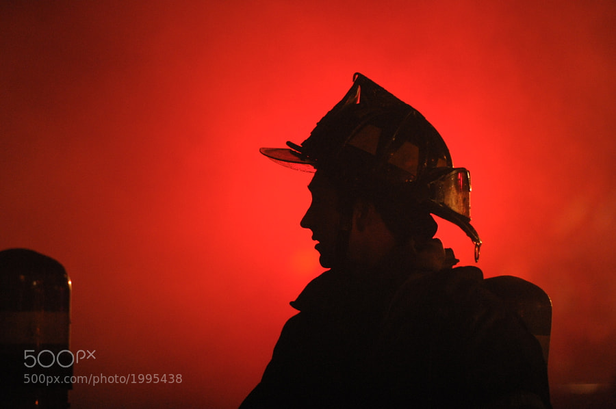 A fireman communicates with others during a large structure fire.