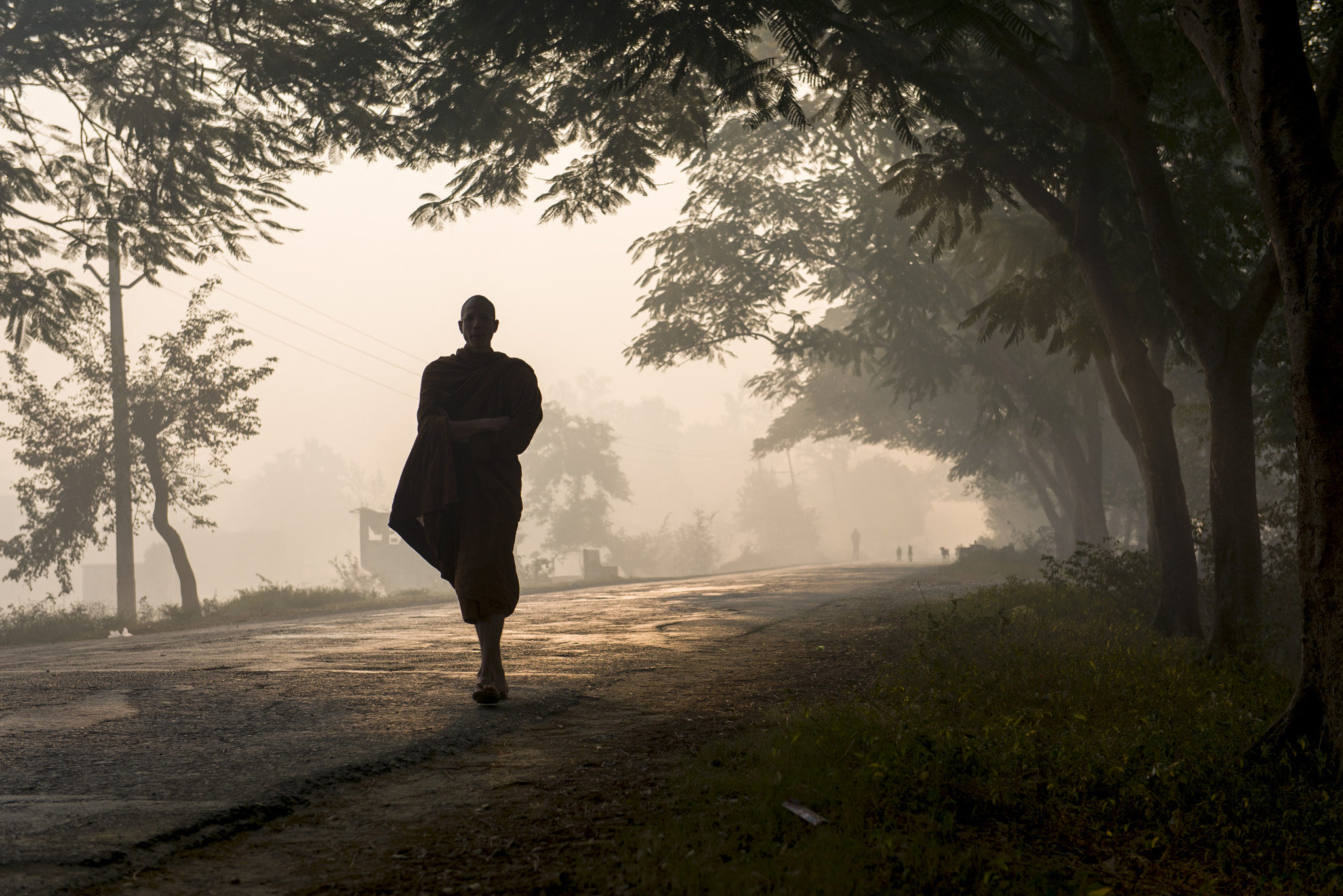 Photograph Monk Walking Through The Morning Fog by Tri Sanguanbun on 500px