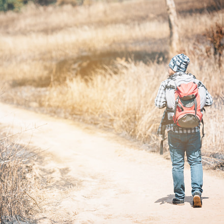 hipster young man with backpack enjoying in area forest