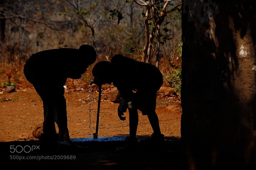 Two Zambian school boys stop for a refreshing drink of clean water.