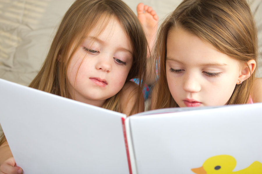 Little girls reading a story together by Mark Carper on 500px.com