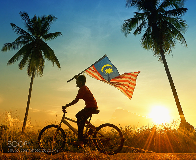 young boy riding bicycle with Malaysian flag