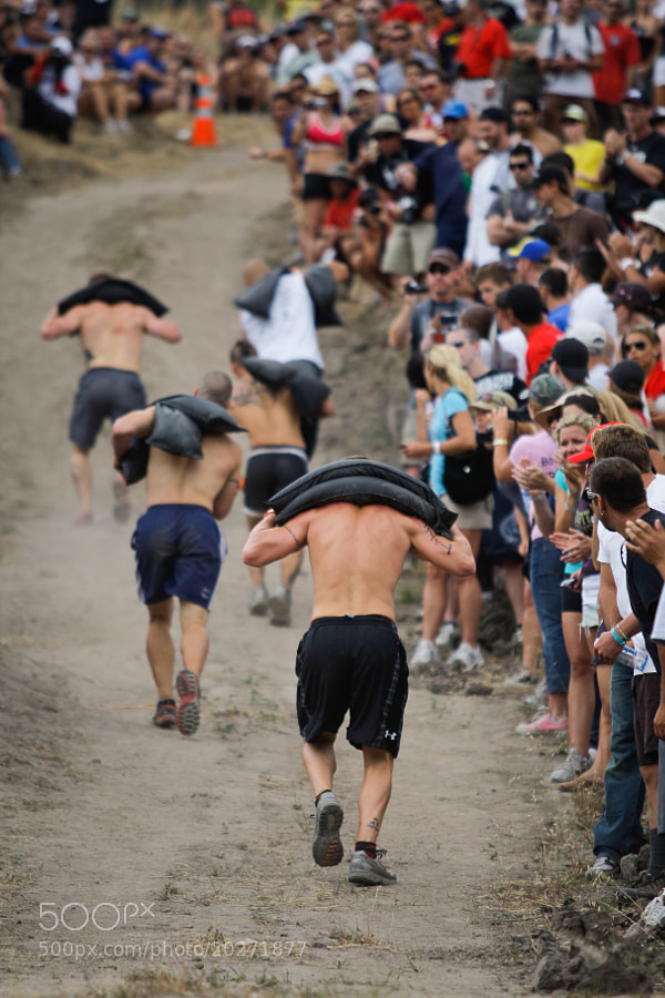 Athletes sprint to the top of a steep hill carrying 70 pounds of sand bags in the 3rd workout of the 2009 CrossFit Games.