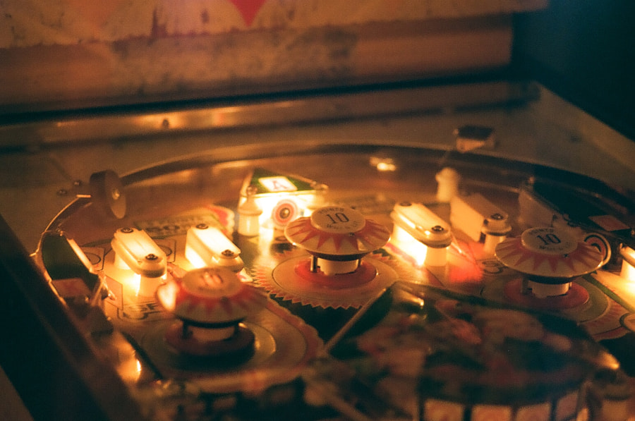 Close-up of a warm, glowing pinball machine. Several components are lit up.