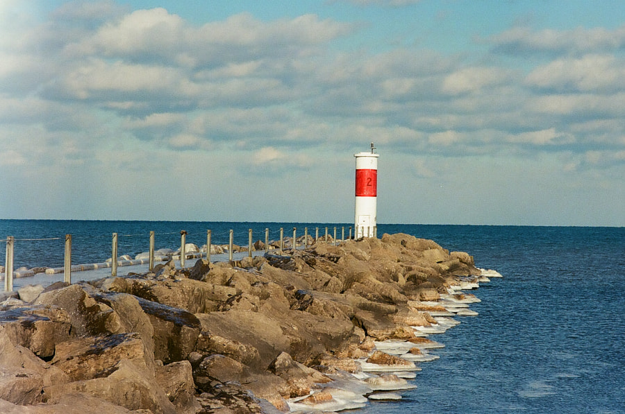 On a partly cloudy day, a rocky pier juts out into the deep blue water. At the end of the pier sits a stout red-and-white lighthouse. The path, as well as the rocks, are covered in ice.