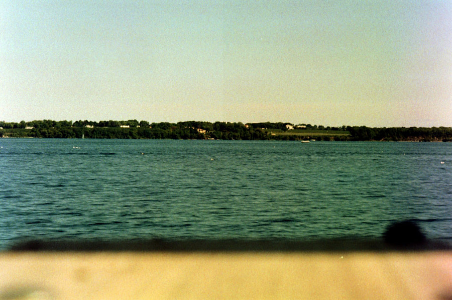 Low-fidelity view of lakewater, with trees and grass far in the background.